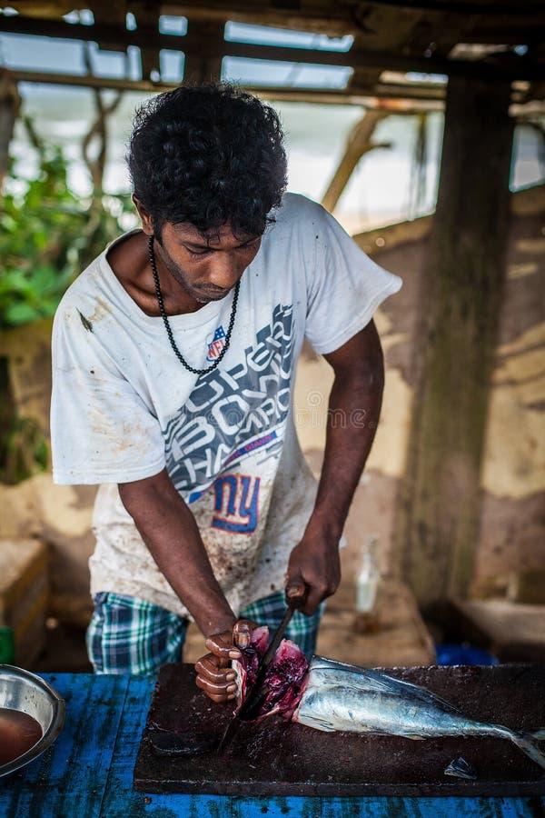 Малознакомые рыбы молодого человека палачествуя с большим ножом грязная работа Трудный деятеля рыболов мясник держа рыб стоковое фото