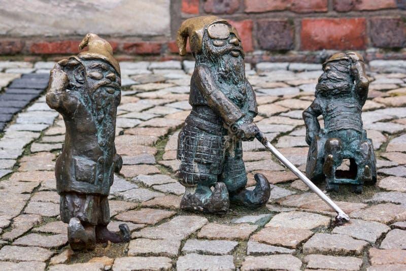 Малые бронзовые гномы по имени - Gluchak статуи глухое, выведенные из строя шторка Slepak и W-Skers, группа в составе гном 3 стоковое фото rf