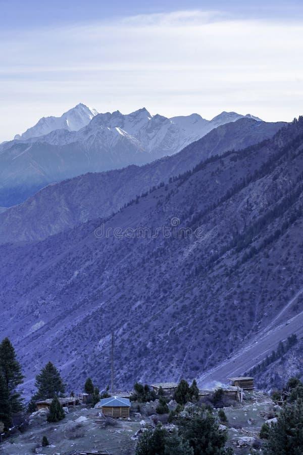 Малые деревянные коттеджи в долине с backg высокой горы стоковые изображения rf