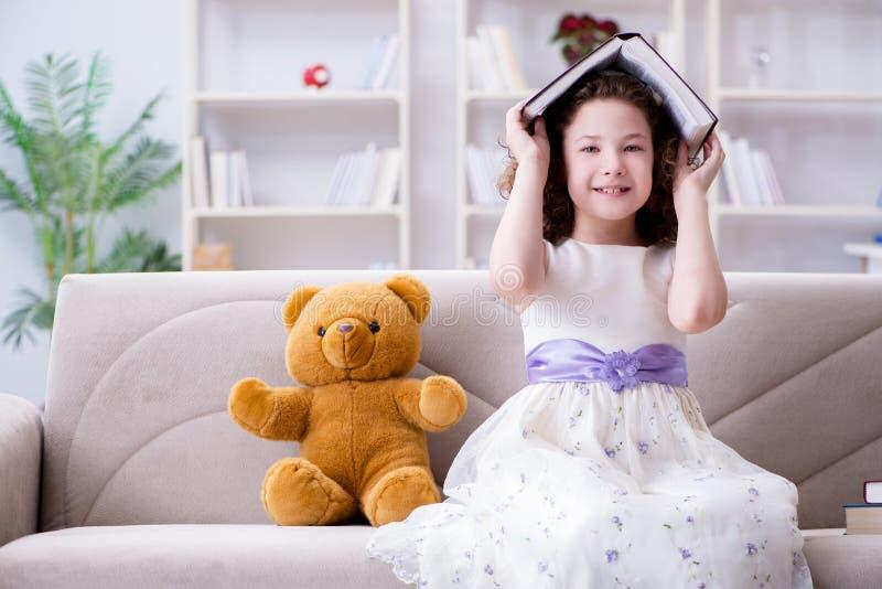 Малые книги чтения девушки дома стоковые фото