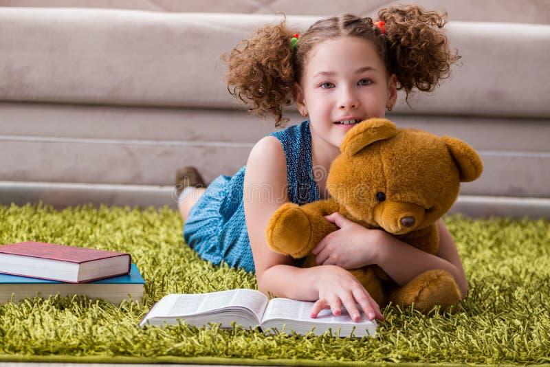 Малые книги чтения девушки дома стоковые изображения
