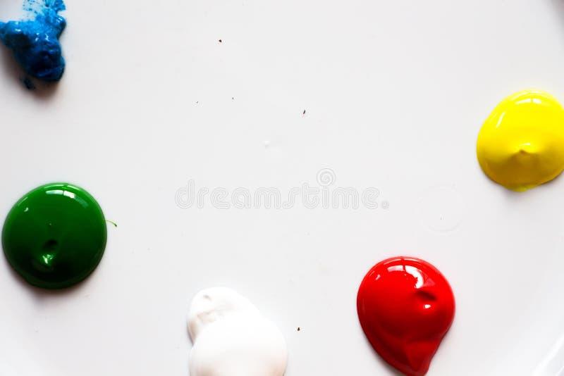 Малые падения краски лежат на белой поверхности Эта краска готова для рисовать и создавать новые чертежи стоковые изображения rf