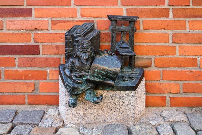 Малый бронзовый гном по имени - Drukarz Kacper статуи, гном с печатным станком стоковая фотография rf