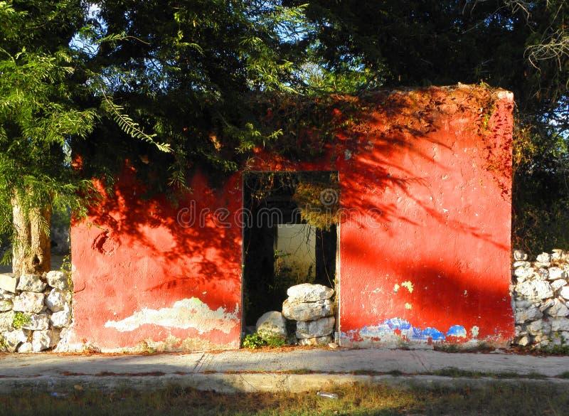 Малый загубленный дом с красным фасадом в покинутом крупном поместье в Юкатане, Мексике стоковые изображения rf