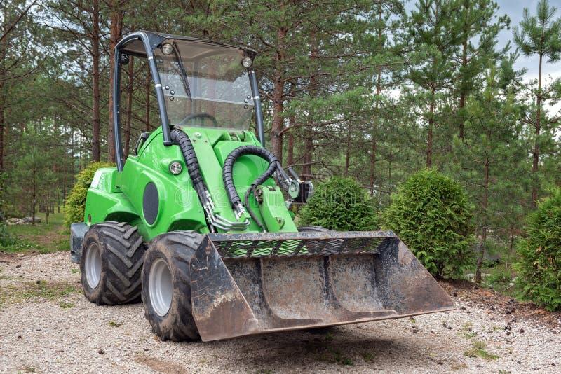 Малый зеленый затяжелитель трактора или скида припарковал в лесе стоковые изображения rf