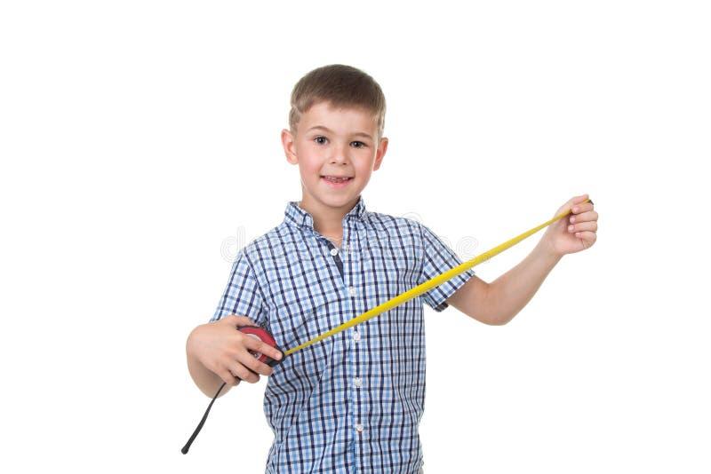 Малый красивый мальчик построителя одел в голубых checkered владениях рубашки измеряя ленту, изолированную на белой предпосылке стоковые фотографии rf