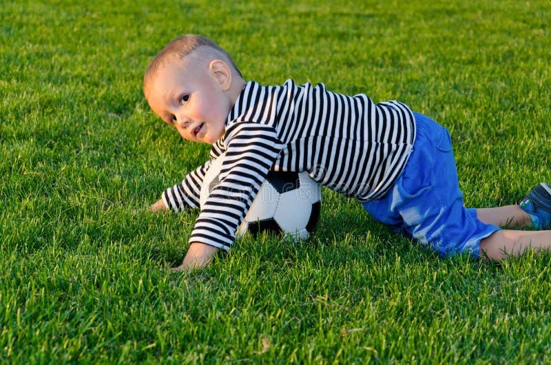 Малый мальчик играя футбол стоковое изображение rf