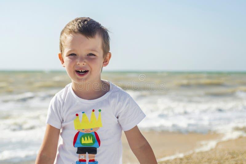 Малый мальчик идя на пляж стоковые изображения