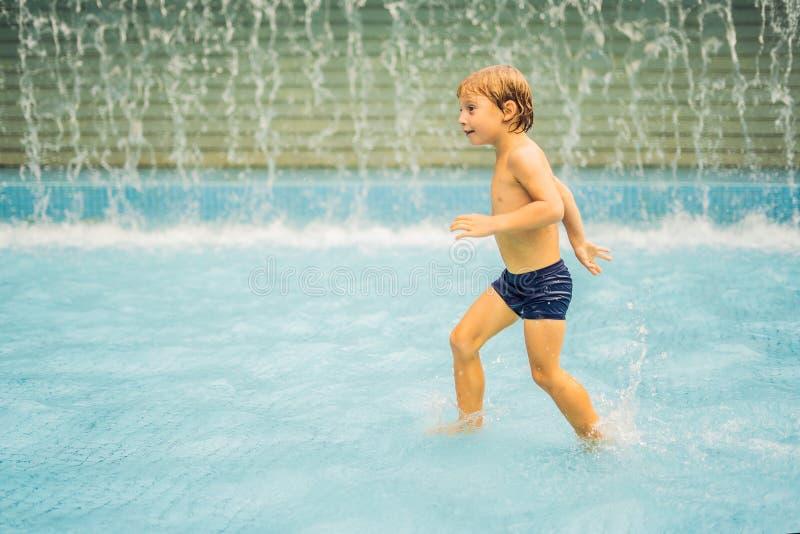 Малый мальчик имея потеху бежать в бассейне стоковое изображение rf