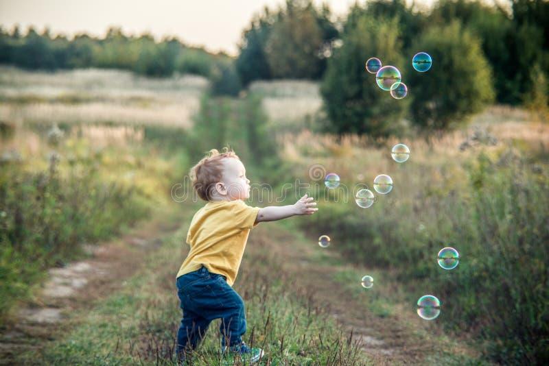 Малый мальчик ребенк играя с пузырями мыла стоковые изображения