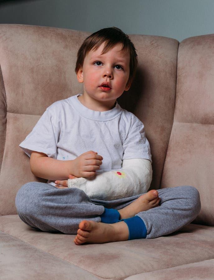 Малый мальчик сидит на стуле с сломленной рукой, в больнице бросания Медицина опасность боль сломать лимбы расправа стоковое фото rf