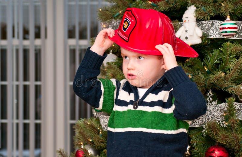 Малый мальчик с шлемом пожарного стоковое изображение rf