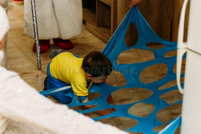 малый мальчик шагает сверх, подъемы, рельсы, пропуски в отверстие, отрезок, отверстие в голубой ткани, в деле Игра ребенка тоннел стоковое изображение