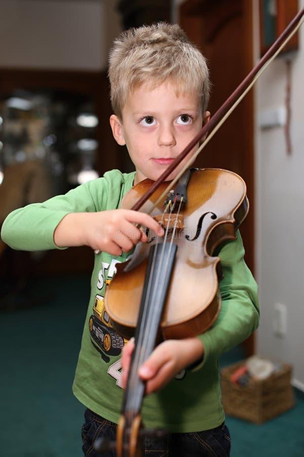 Малый мальчик thruming на скрипке в комнате стоковые изображения rf