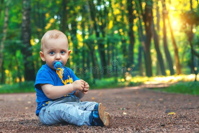 Малый милый младенец с ниппелью сидит на тропе в сказочном лесе совсем самостоятельно Мальчик сидя на том основании стоковые изображения rf