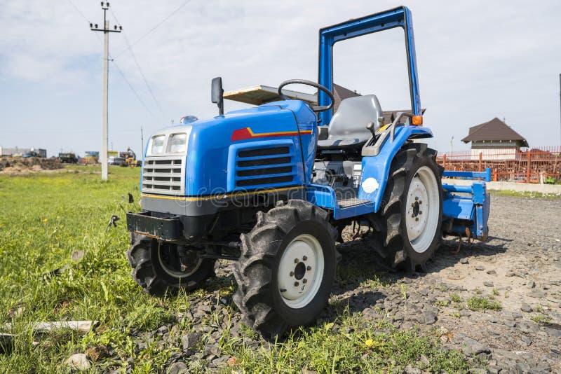 Малый мини голубой трактор стоит на дворе фермы на зеленой траве и ждет работу для того чтобы начать стоковые фотографии rf