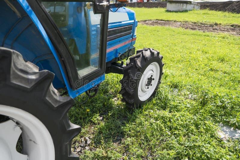 Малый мини голубой трактор стоит на дворе фермы на зеленой траве и ждет работу для того чтобы начать стоковое фото rf