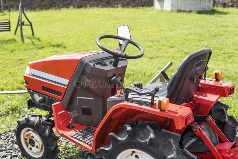 Малый мини красный трактор стоит на дворе фермы на зеленой траве и ждет работу для того чтобы начать стоковые фотографии rf