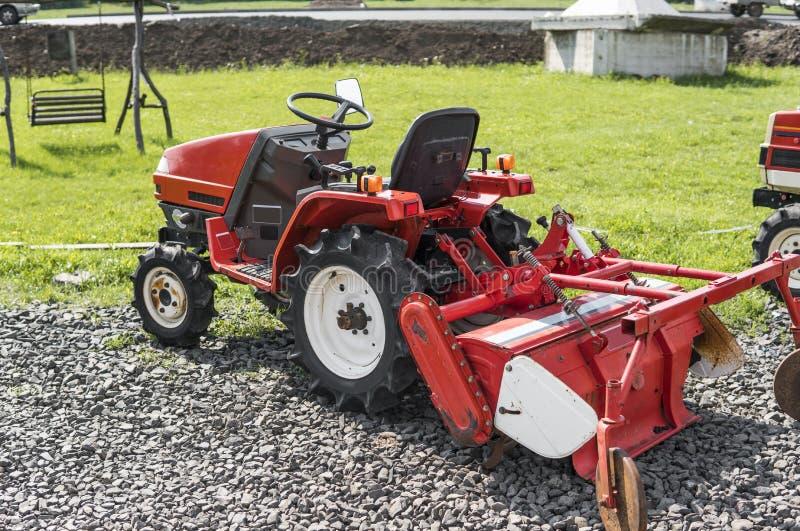 Малый мини красный трактор стоит на дворе фермы на зеленой траве и ждет работу для того чтобы начать стоковое фото rf