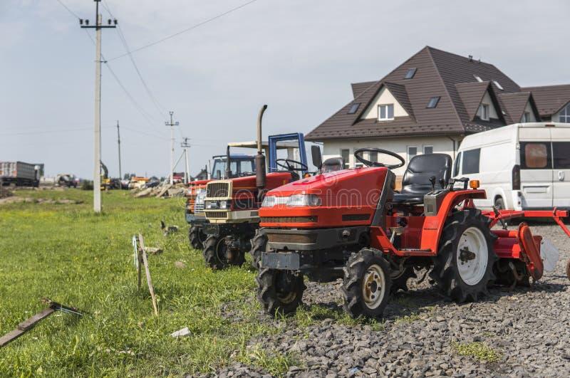 Малый мини красный трактор стоит на дворе фермы на зеленой траве и ждет работу для того чтобы начать против других тракторов и стоковое фото