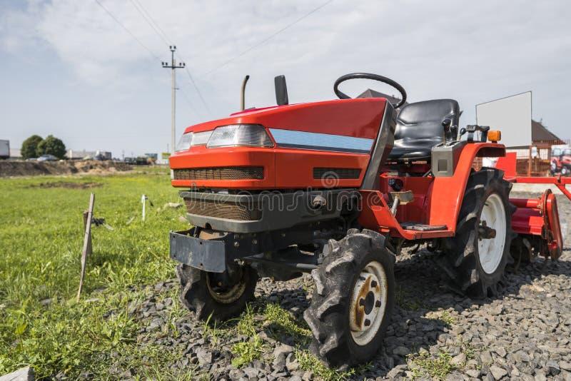 Малый мини красный трактор стоит на дворе фермы на зеленой траве и ждет работу для того чтобы начать стоковая фотография