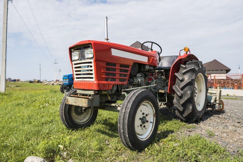 Малый мини красный трактор стоит на дворе фермы на зеленой траве и ждет работу для того чтобы начать стоковые изображения rf