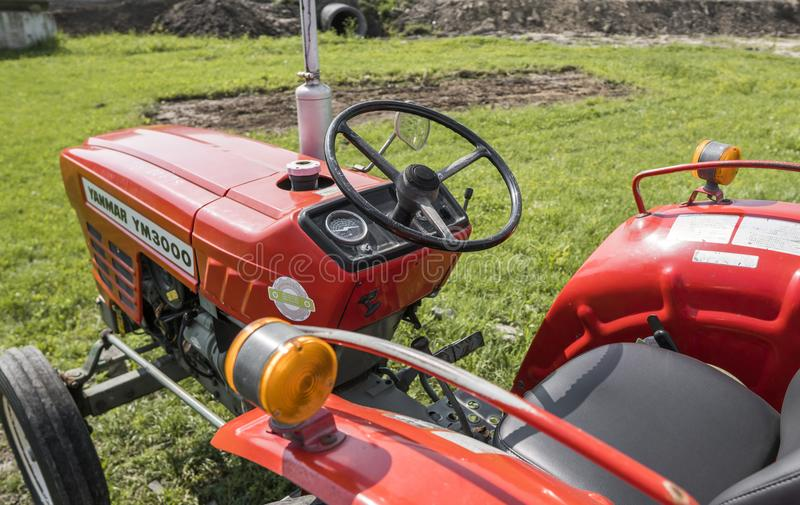 Малый мини красный трактор стоит на дворе фермы на зеленой траве и ждет работу для того чтобы начать стоковая фотография rf