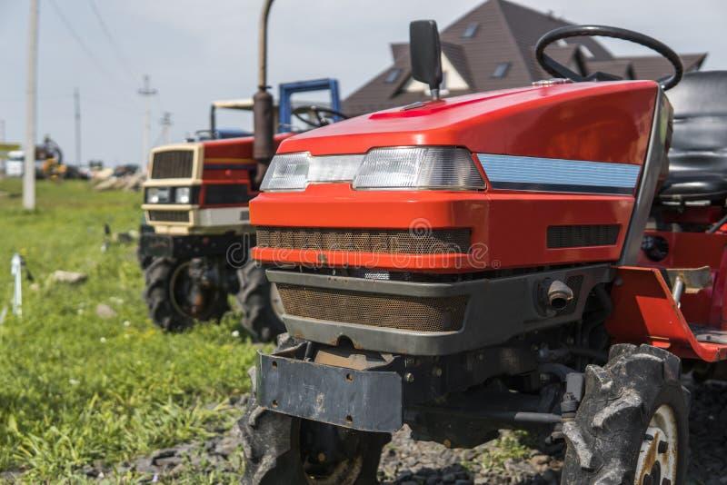 Малый мини красный трактор стоит на дворе фермы на зеленой траве и ждет работу для того чтобы начать стоковое изображение