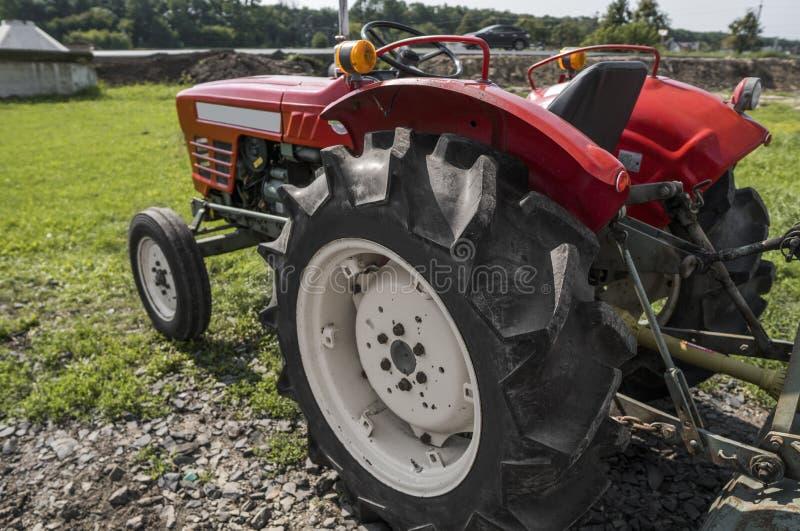 Малый мини красный трактор стоит на дворе фермы на зеленой траве и ждет работу для того чтобы начать стоковые изображения