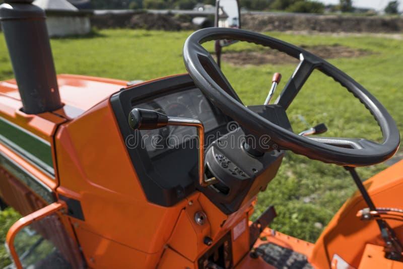 Малый мини оранжевый трактор стоит на дворе фермы на зеленой траве и ждет работу для того чтобы начать стоковая фотография rf