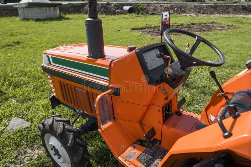 Малый мини оранжевый трактор стоит на дворе фермы на зеленой траве и ждет работу для того чтобы начать стоковые изображения rf