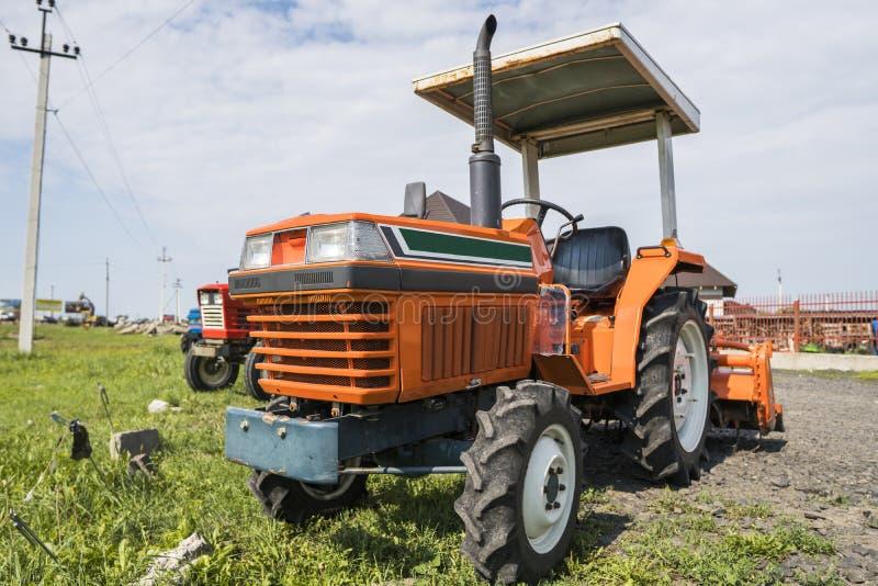 Малый мини оранжевый трактор стоит на дворе фермы на зеленой траве и ждет работу для того чтобы начать стоковые изображения