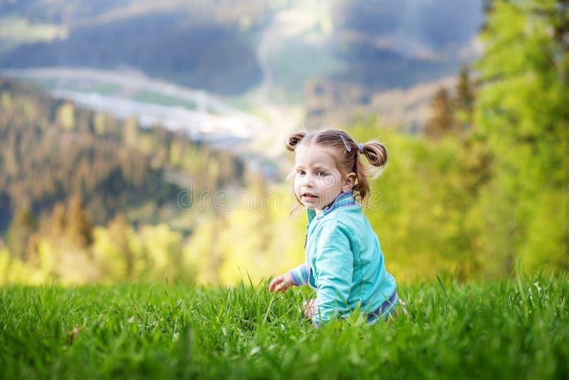 Малый младенец сидя на траве Лето Концепция перемещения, стоковые фотографии rf