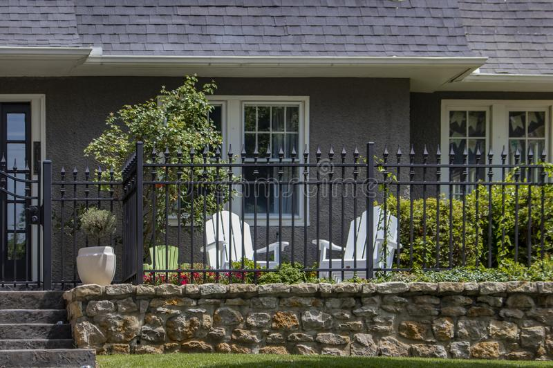Малый ограженный район сада вне входа к дому штукатурки с 2 взрослыми стульями и одним стулом childs стоковая фотография rf