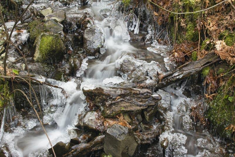 Малый поток с сосульками в зиме стоковое фото rf