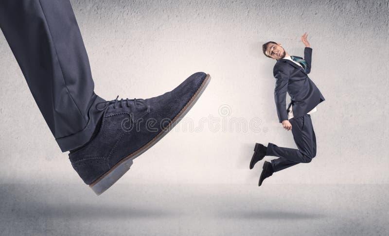 Малый предприниматель пнутый большим ботинком стоковые изображения