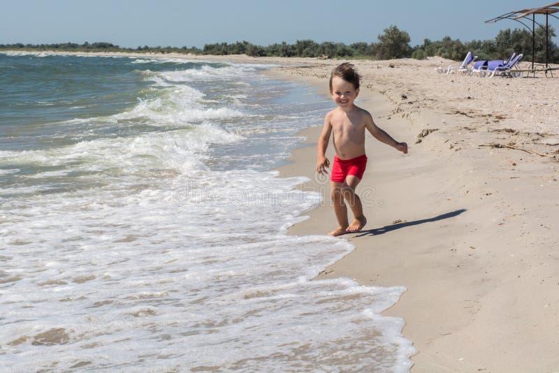 Малый ребенок бежит вдоль seashore испуганного волос волны превращается в ветре, стоковое фото rf