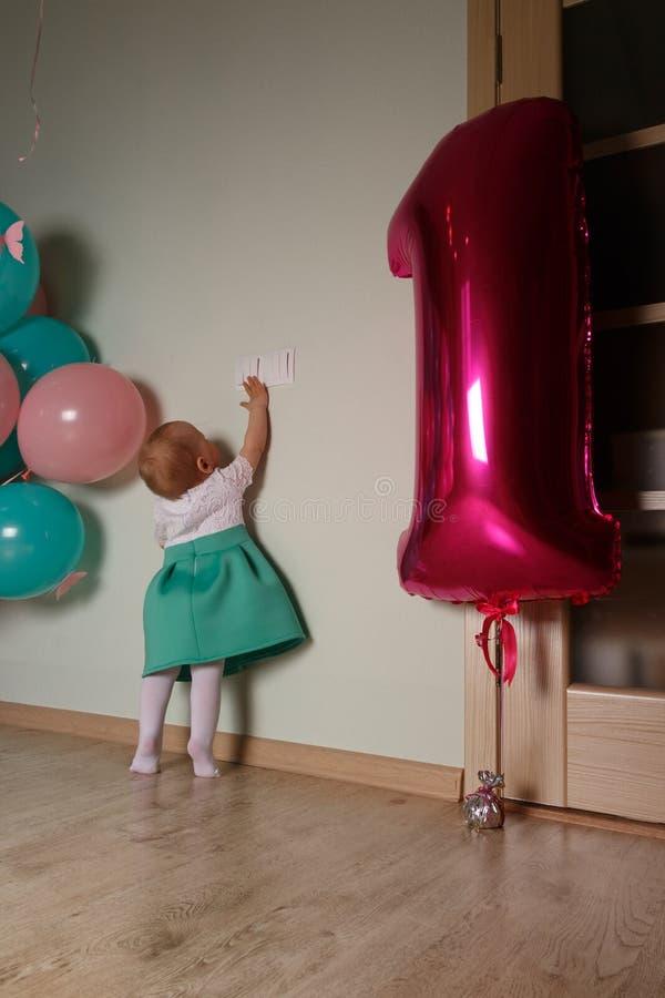 малый ребенок достигая для выключателя, близко воздушные шары, первый день рождения Любопытство девушка в белом голубом платье стоковое фото rf