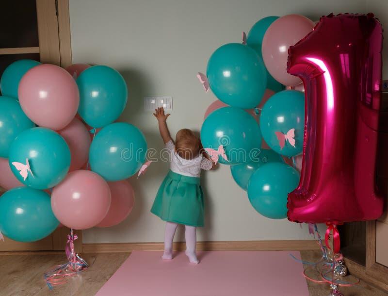 малый ребенок достигая для выключателя, близко воздушные шары, первый день рождения Любопытство стоковые фотографии rf