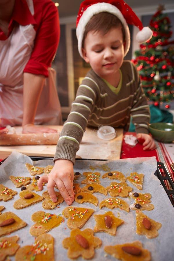 Малый ребенок помогая с тортом рождества стоковая фотография rf