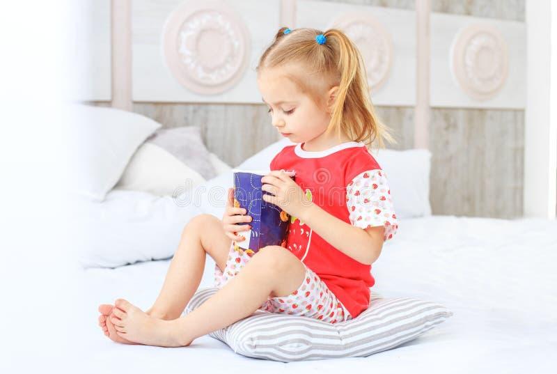 Малый ребенок сидя на кровати в его пижамах Концепция  стоковая фотография