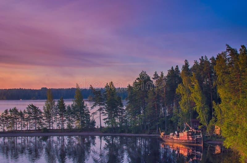 Малый рыболовецкий или прогулочный катер, пришвартованный на озере Пайянн Прекрасный пейзаж с каменным пляжем, сосновым лесом и в стоковые изображения rf