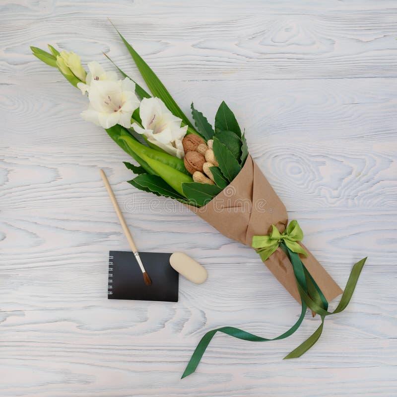 Малый скромный букет состоя из гладиолуса, гаек, канцелярских принадлежностей на белом деревянном столе как подарок к ребенку шко стоковые изображения