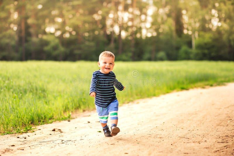 Малый смеясь над мальчик бежит вдоль дороги леса стоковое фото rf