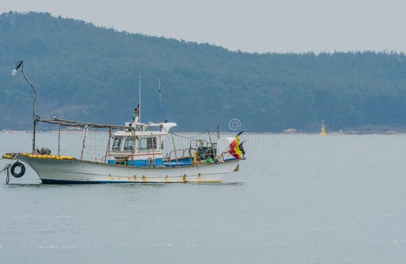Малый траулер рыбной ловли мирно плавая в воду стоковое изображение rf