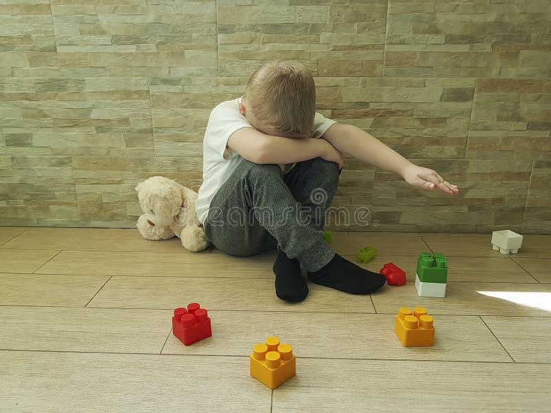 Малый унылый мальчик сидя на нежности осадки пола несчастной frustratedsadness депрессии блока стоковое фото rf