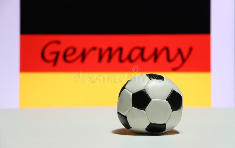 Малый футбол на белом поле и немецкая нация сигнализируют с текстом предпосылки Германии стоковые фотографии rf