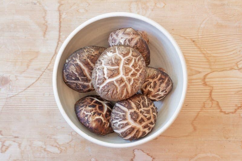 Малый шар высушенных крышек гриба шиитаке центризовал на выдержанной деревянной предпосылке стоковое изображение