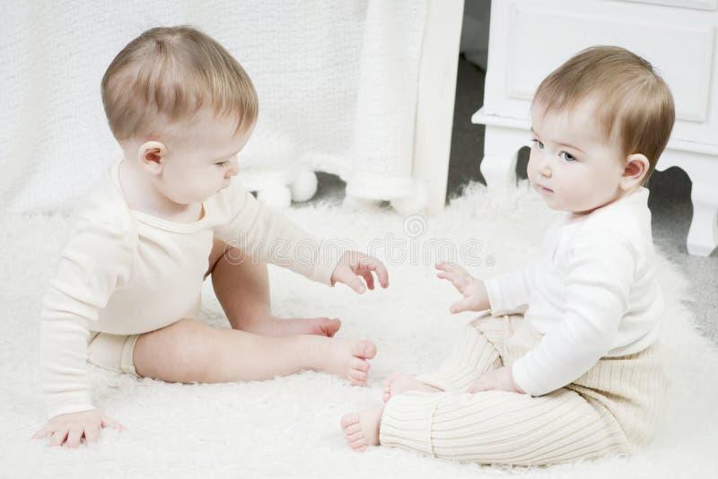 2 малых дет, мальчик и девушка в естественных пеленках ткани, естественный swaddling, дружественные к эко хлопко-бумажные ткани стоковое фото