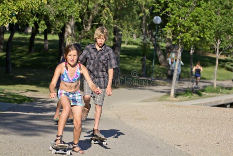 малыши едущ скейтборд их стоковые изображения